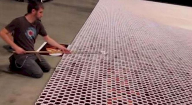 Il aligne plus de 66 000 verres sur le sol. Lorsque la caméra dézoome, c'est hallucinant!