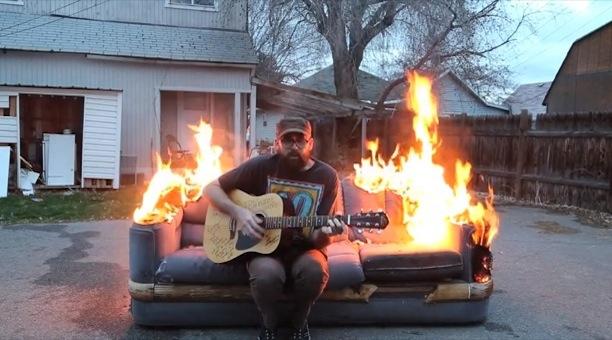 Il joue de la guitare sur un canapé en feu